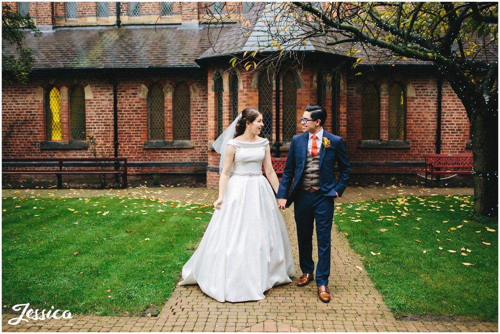 couple walk outside gorton monastery in manchester after their ceremony finishes