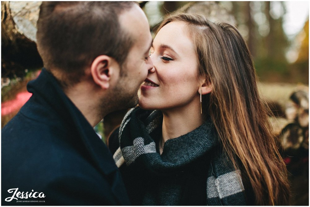 engaged couple kissing in delamere forest in cheshire