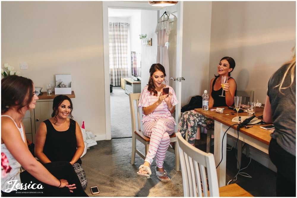 bridesmaids laugh together whilst getting ready for the wedding