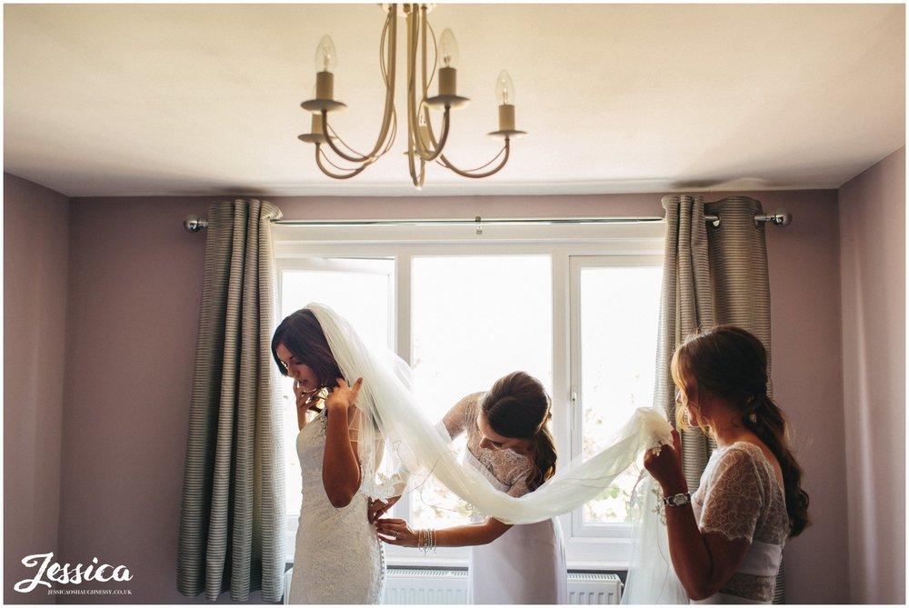 Bridesmaid help the bride into her wedding dress