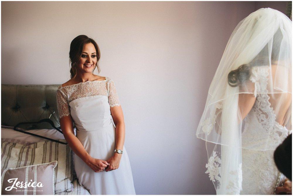 bridesmaid admires the bride in her dress