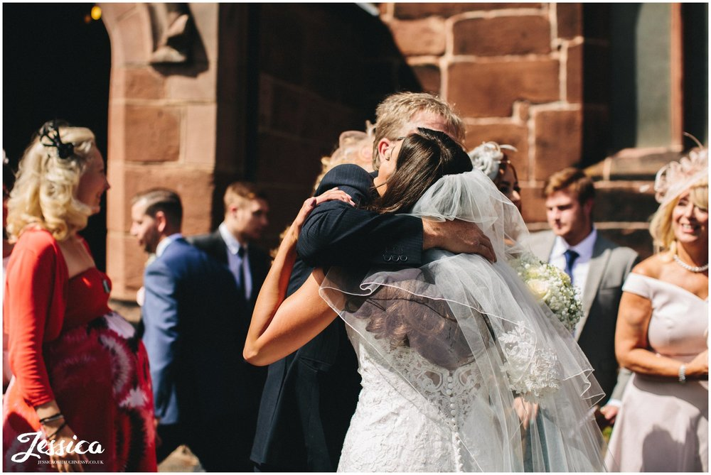 guest hugs the bride outside wirral chuch