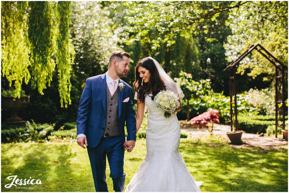 newly married couple walk through brook hall hotel's grounds