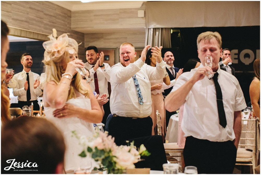 wedding guests cheer after the brook hall hotel speeches end