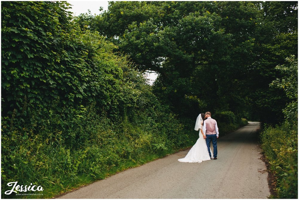 bride & groom kiss in the middle of a country road
