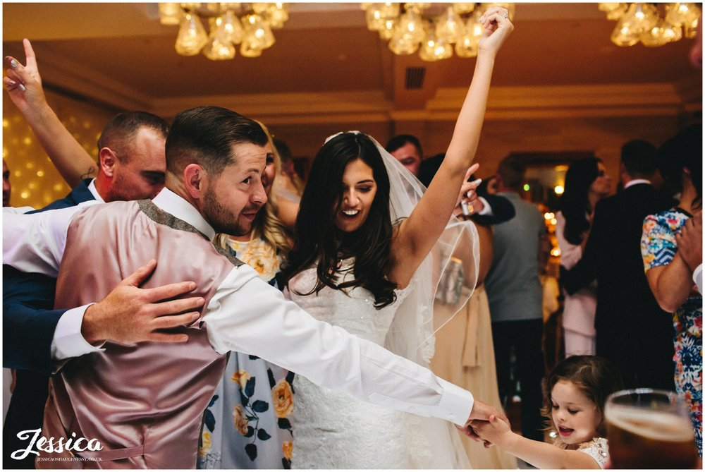 newly wed's hug guests after their first dance ends