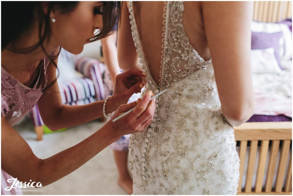 bridesmaid fastens the wedding dress buttons