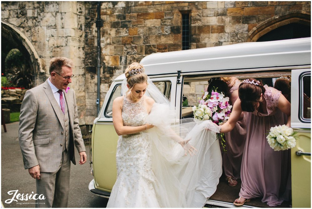 bride gets out of her wedding car for the ceremony