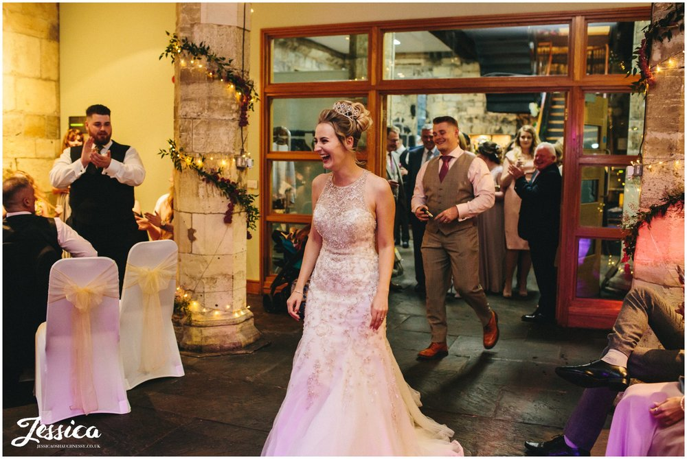 bride enters the room ready for her first dance