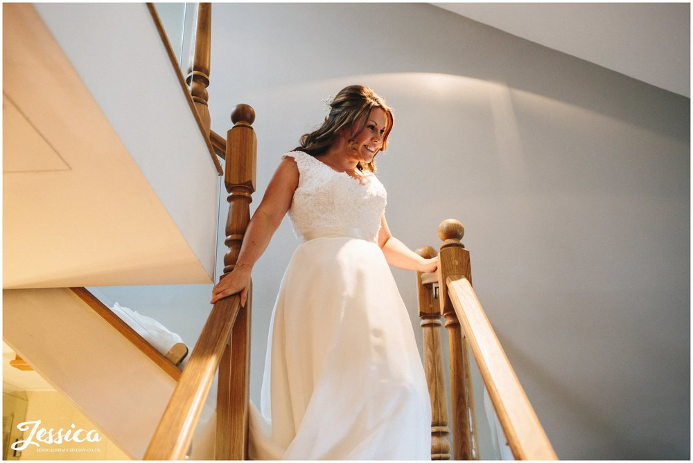 the bride walks downstairs in her wedding dress