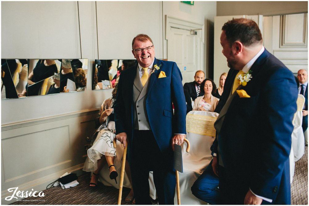 the groom & his father joke as they wait for the bride to arrive
