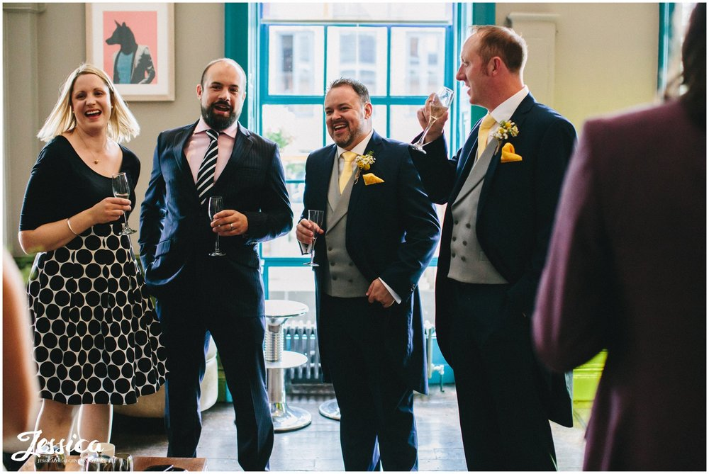 groom laughs with wedding guests at his oddfellows wedding