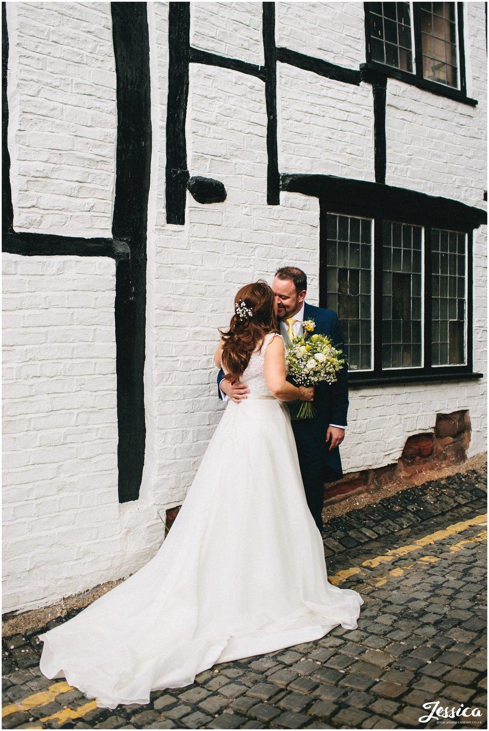 bride & groom kiss outside chester's tudor buildings