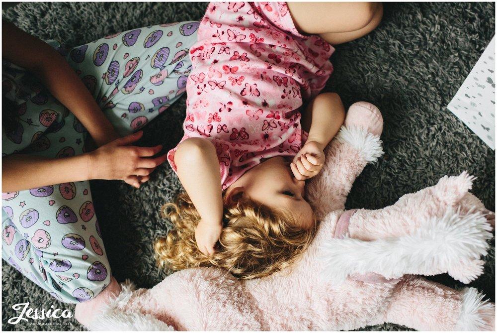 flower girl sleeps on the floor whilst bridesmaids get ready