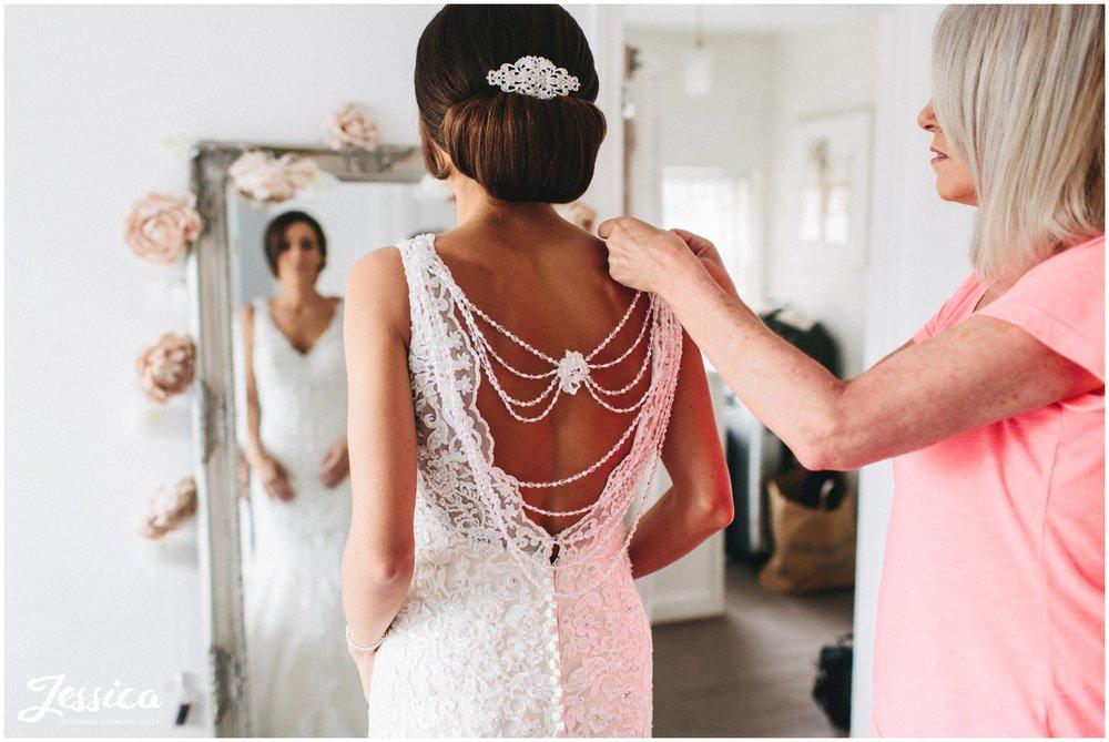 bride's mother helps her daughter into her wedding dress