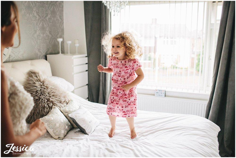 flower girl jumps on bed
