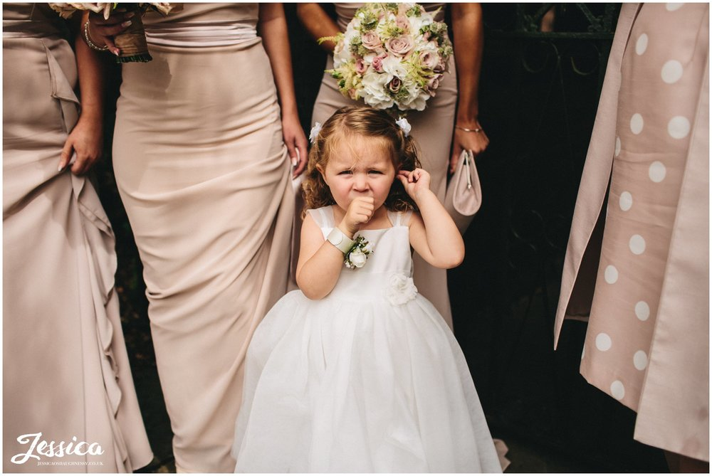 flower girl waits for the bride to arrive outside the church