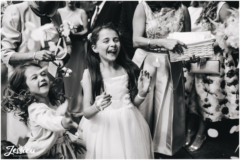 children throw confetti at the newly wed's