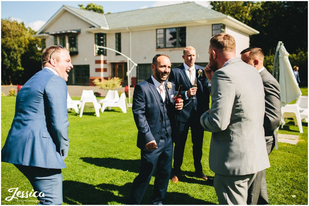 groomsmen laughing in the sun at the wirral wedding