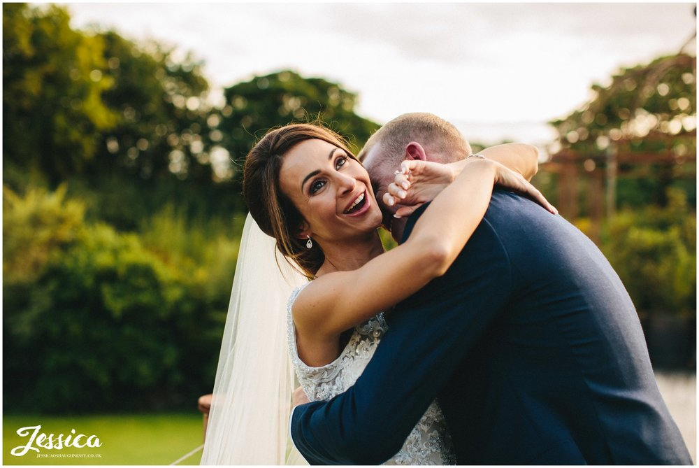 bride laughs as her new husband hugs her