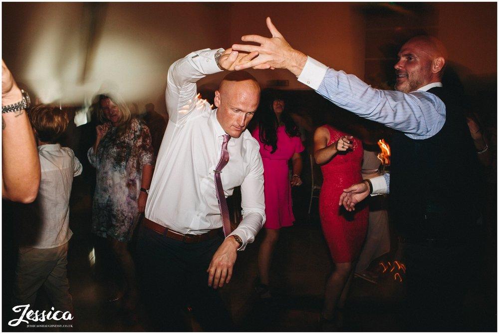 men dance together on the dancefloor