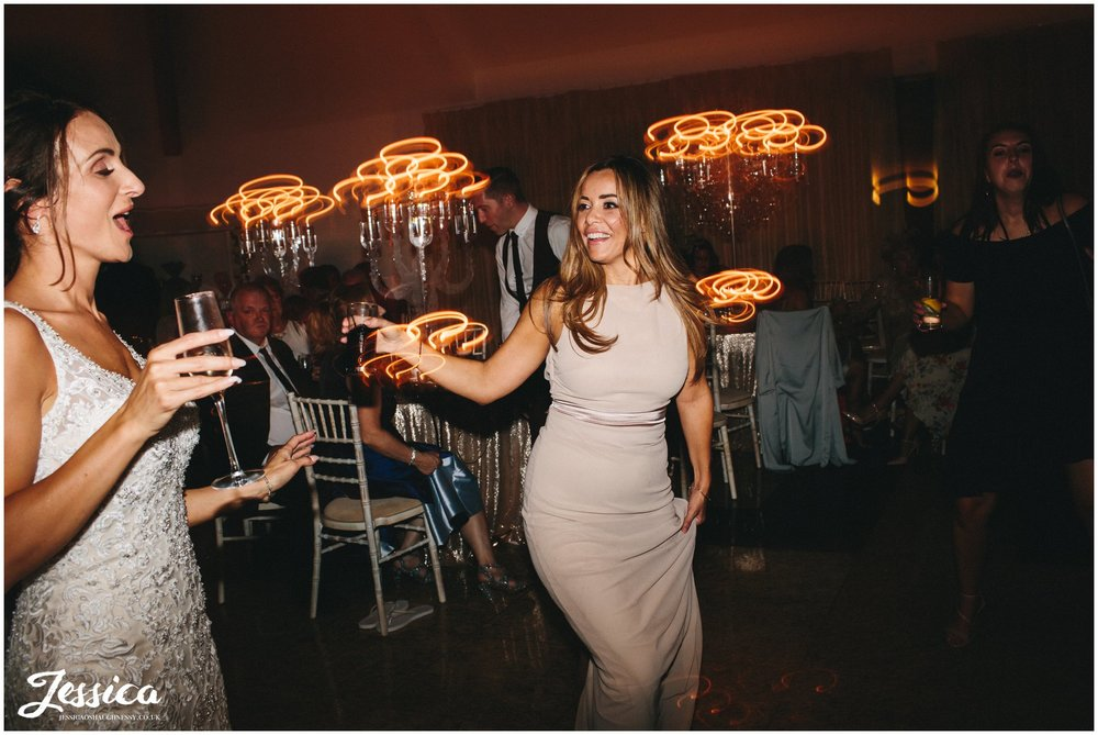 bride dances with her bridesmaid at her wirral wedding