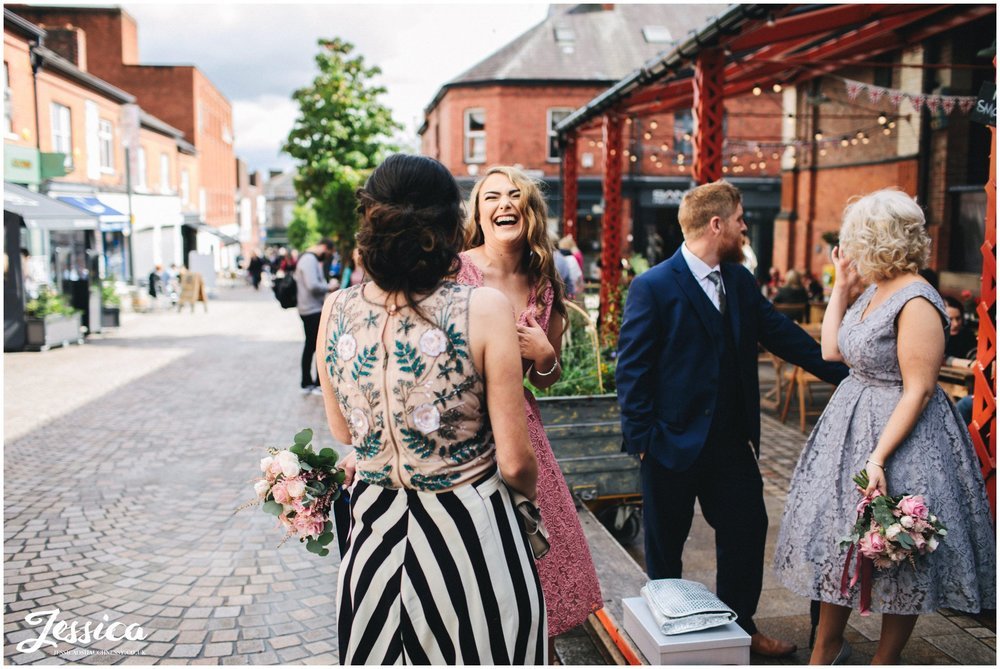 bridesmaid laughs with friends before the wedding ceremony