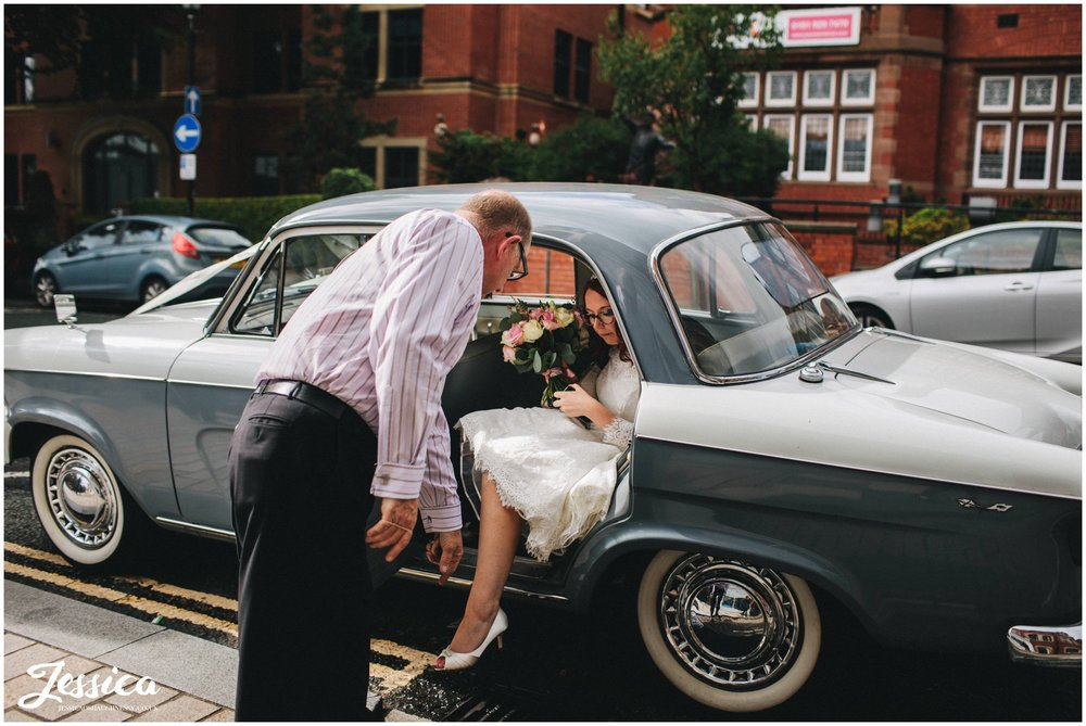 bride gets out of vintage car at altrincham town hall