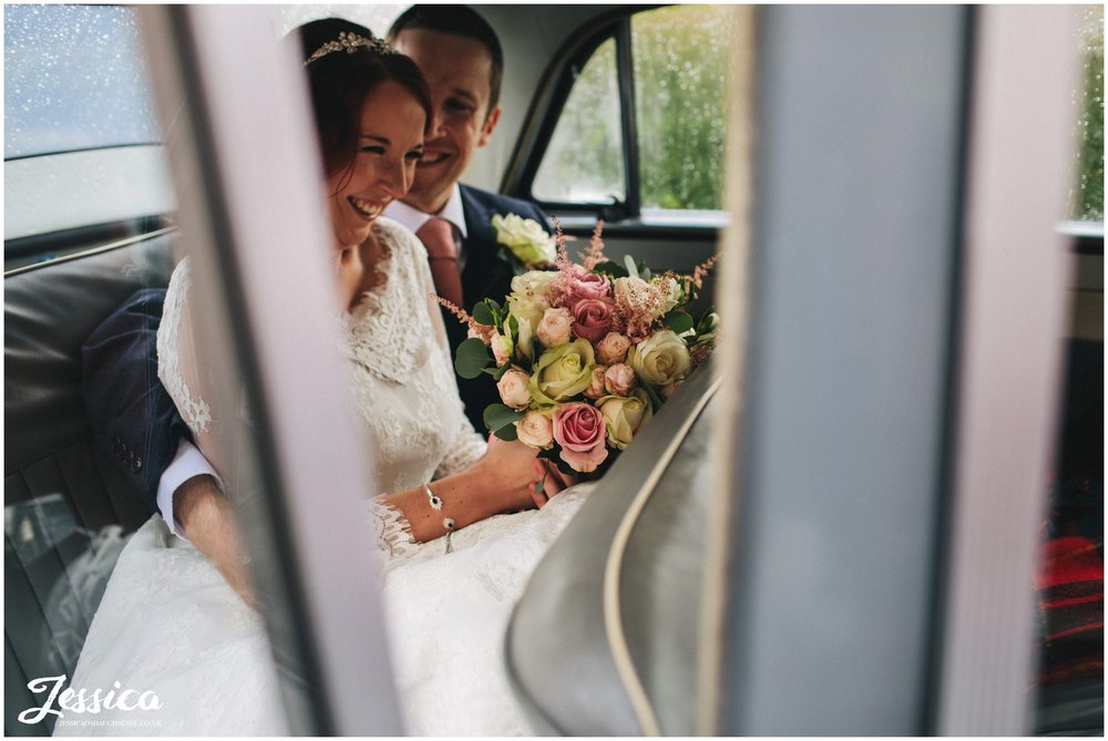 newly wed's laughing together in the back of their wedding car