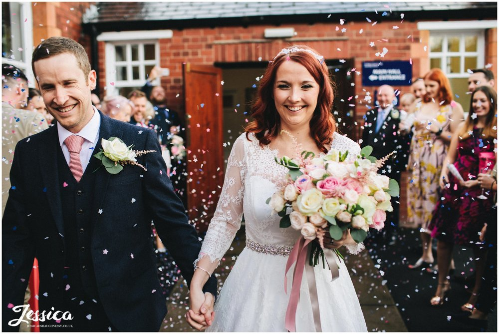 husband and wife walk through their confetti line