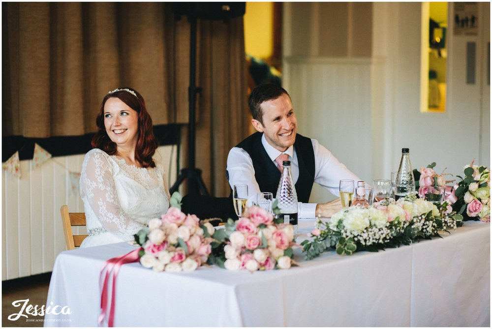 the new couple laugh during their wedding speeches