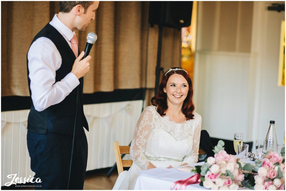 bride laughs as groom gives his speech