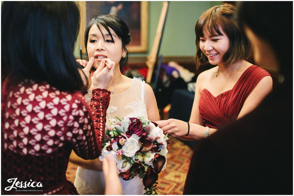 bride touches up lipstick before the ceremony