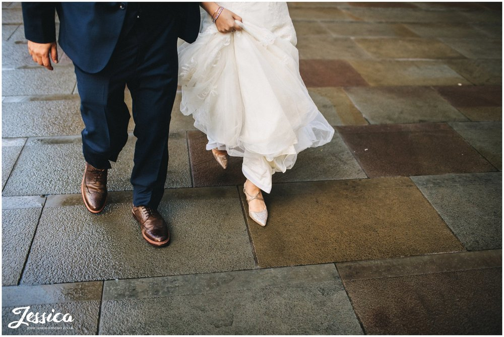 detail shot of newly wed's feet walking through a rainy manchester