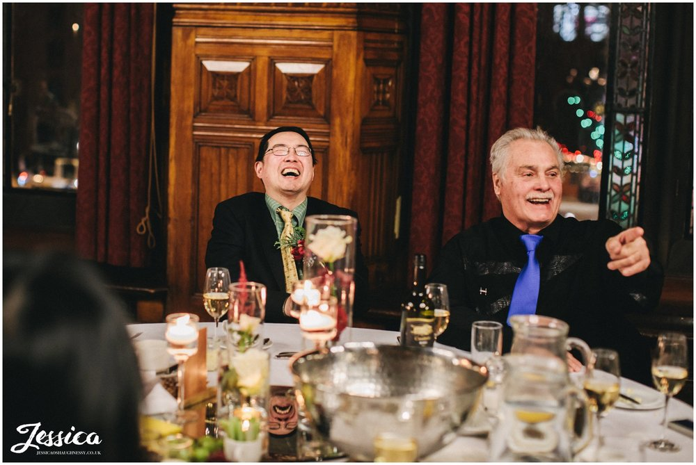 guests laughing during the grooms speech