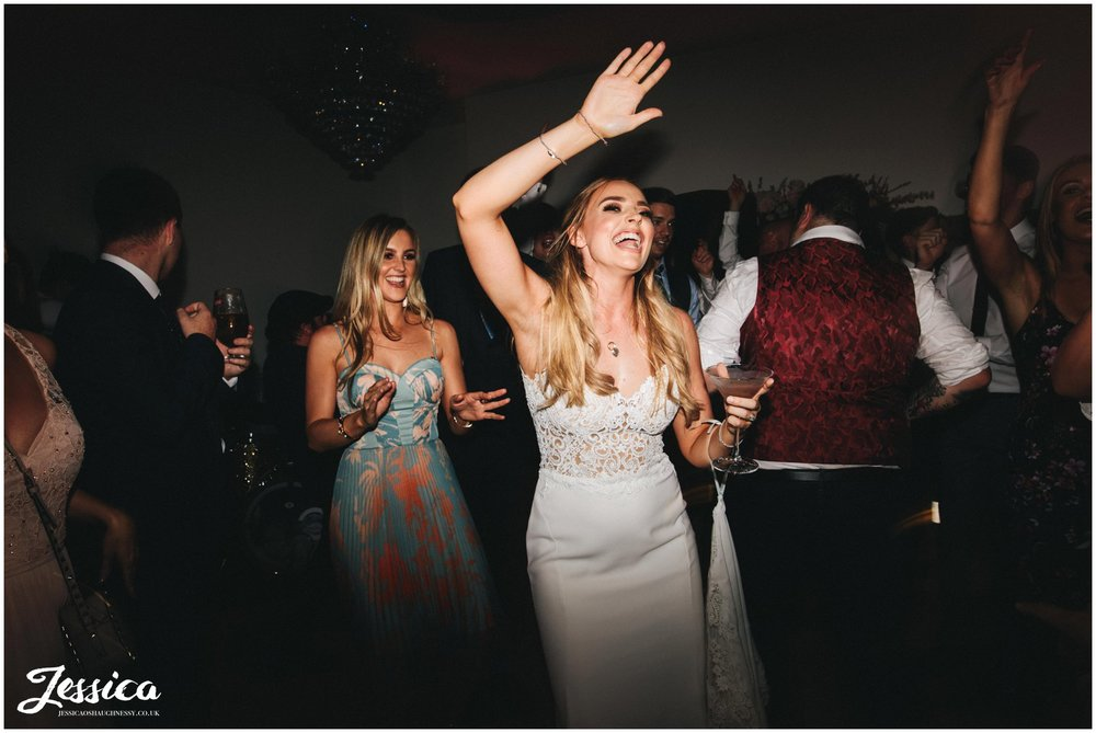 bride dances with her friends to the wedding band