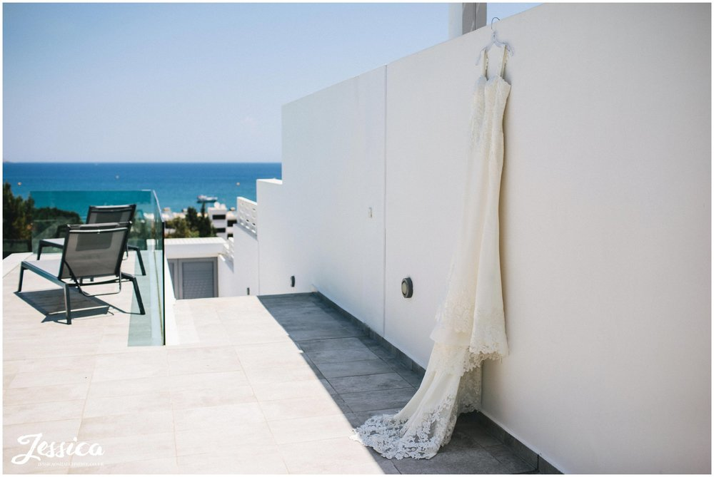 wedding dress hung on the villa wall with the sea in the background
