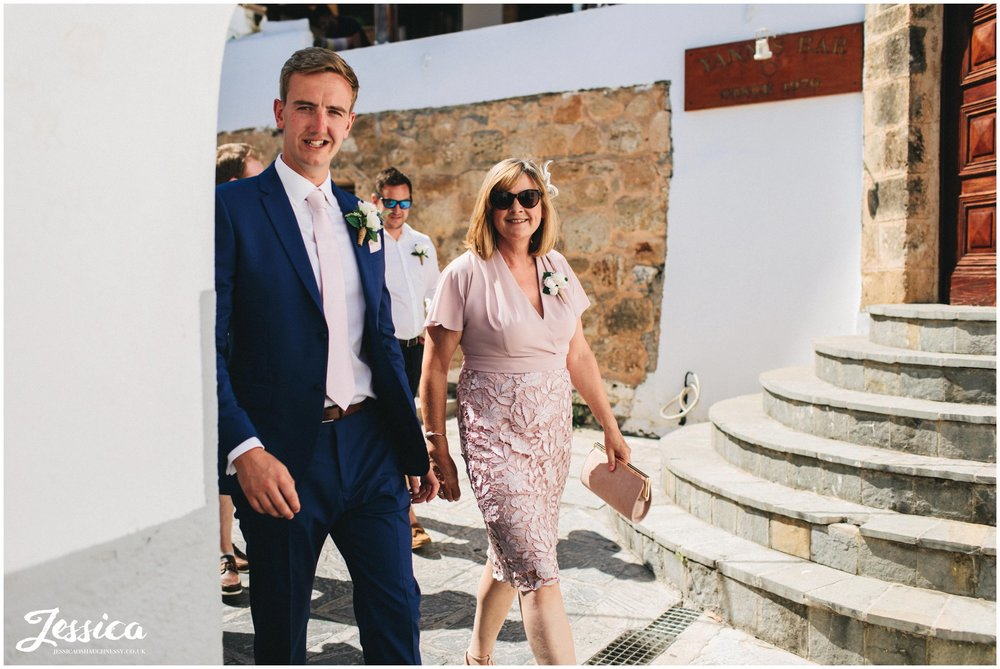 the groom and his mother walk through lindos to st pauls bay