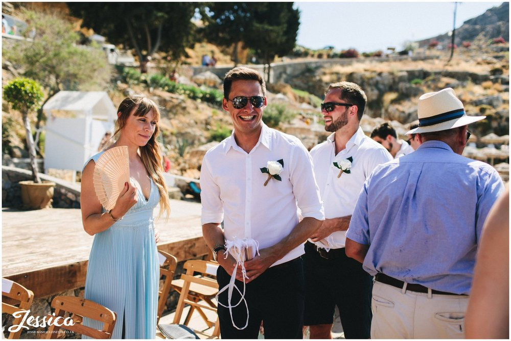 groomsmen hand out fan's for the wedding guests