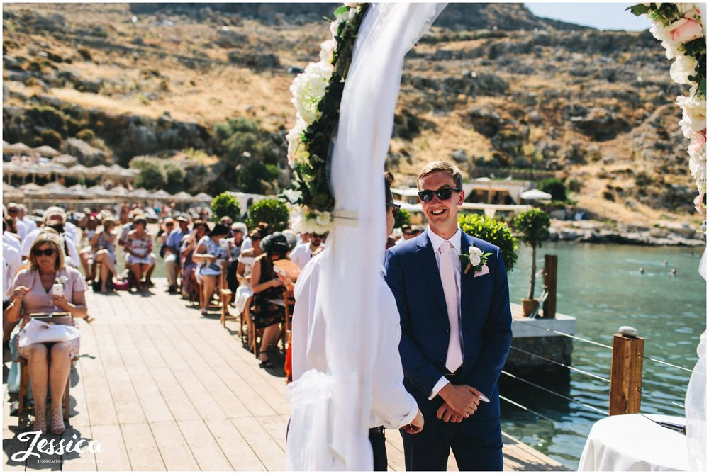 the groom waits for the bride under the flower arch
