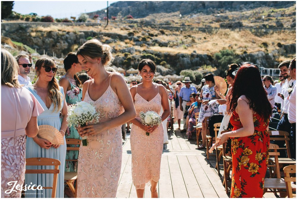 bridesmaids walk down the aisle of the pier at st paul's bay in rhodes