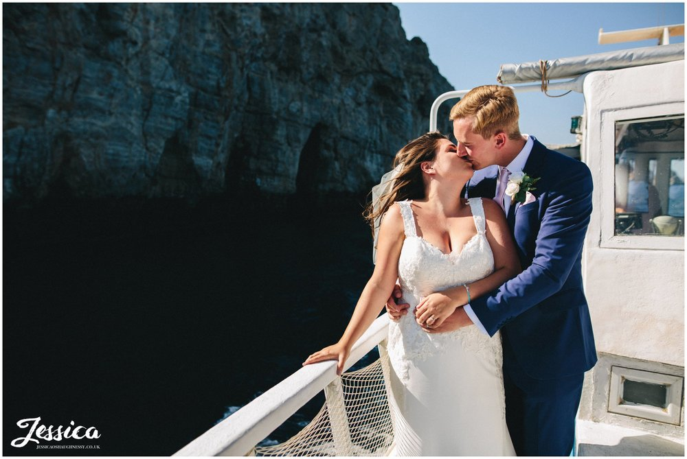 newly wed's kiss on a boat sailing round rhodes island