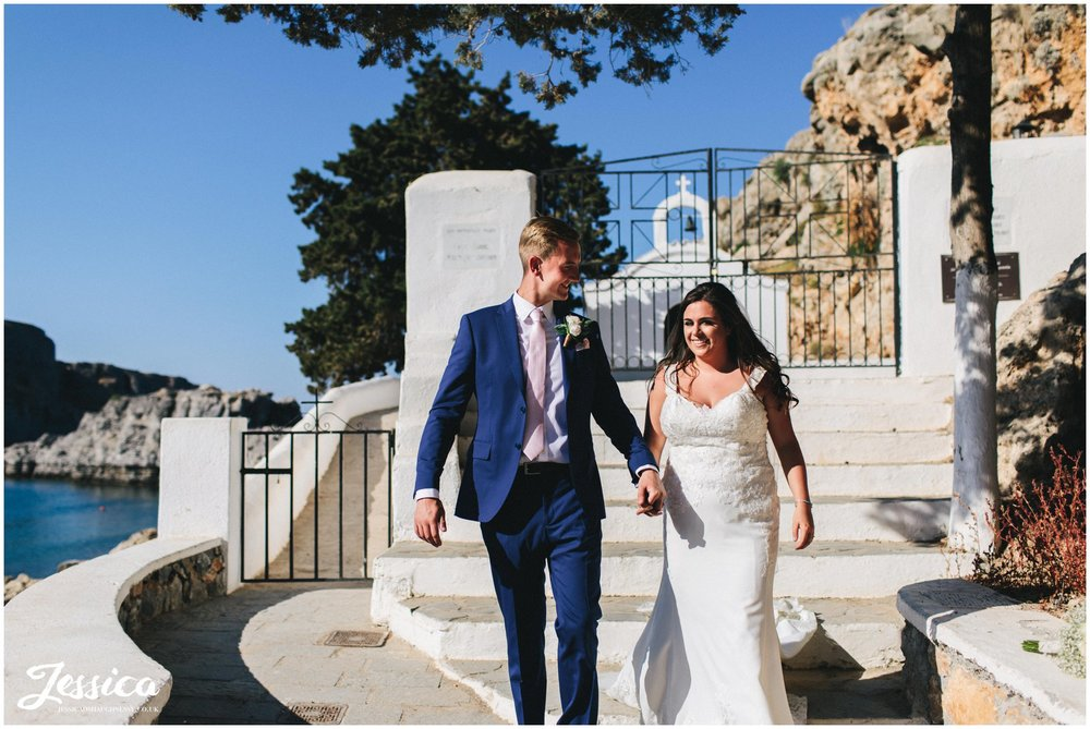 husband and wife walk hand in hand in from of st paul's chapel in rhodes