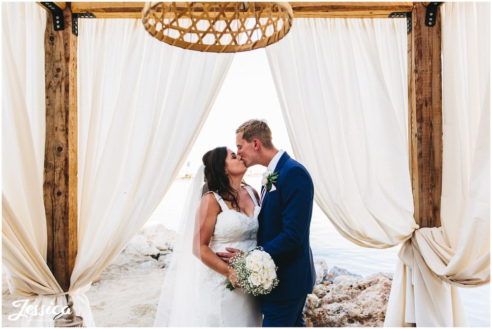 newly wed's kiss under the drapes at Tambakio Restaurant on st paul's bay