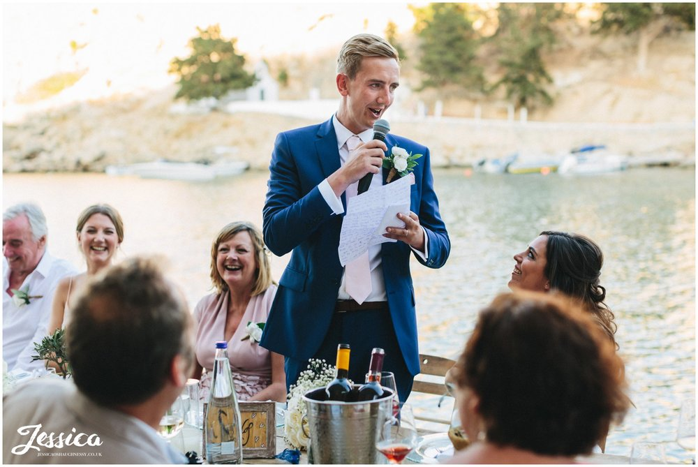 groom gives his speech with the sea in the background
