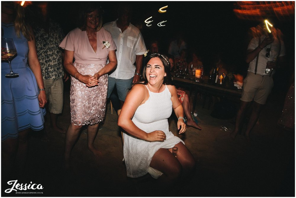 bride sits with a shot on her legs for the groom to find