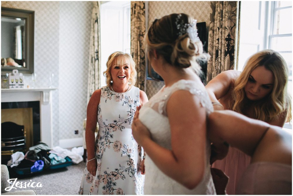 mother of the bride looks proudly at her daughter