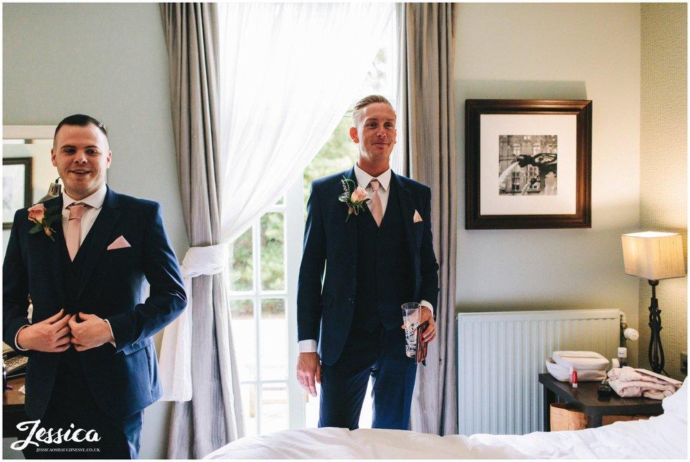 best man looks admire the bride in her wedding dress