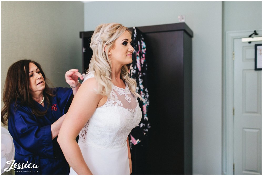 mother of the bride helps her daughter into her dress