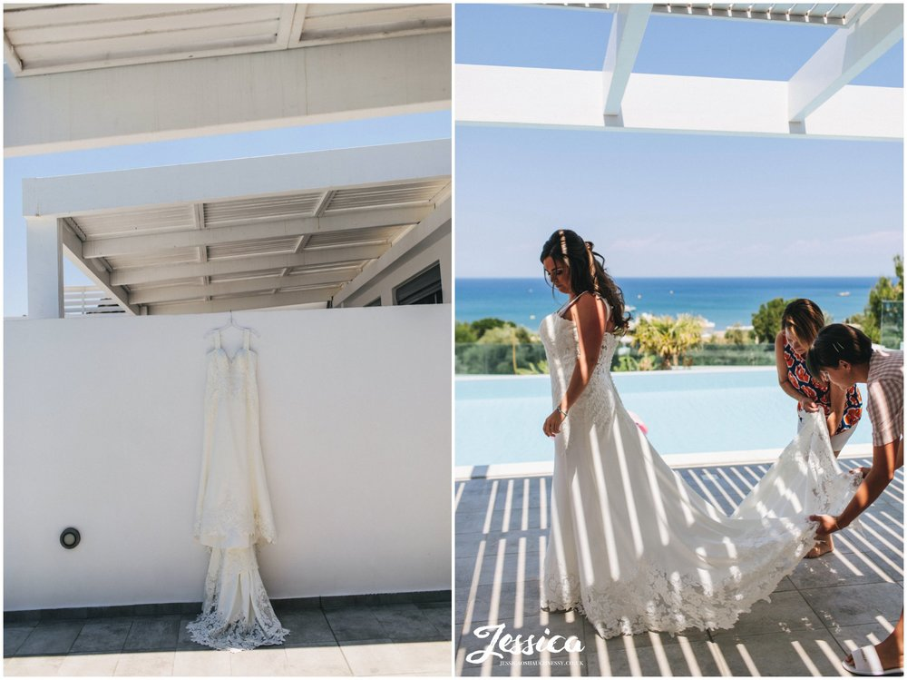 the bride gets into her wedding dress in the sunshine by the pool